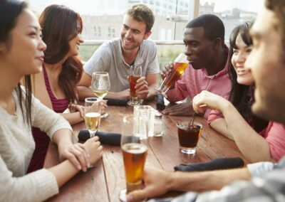 group of people at wooden table drinking beer