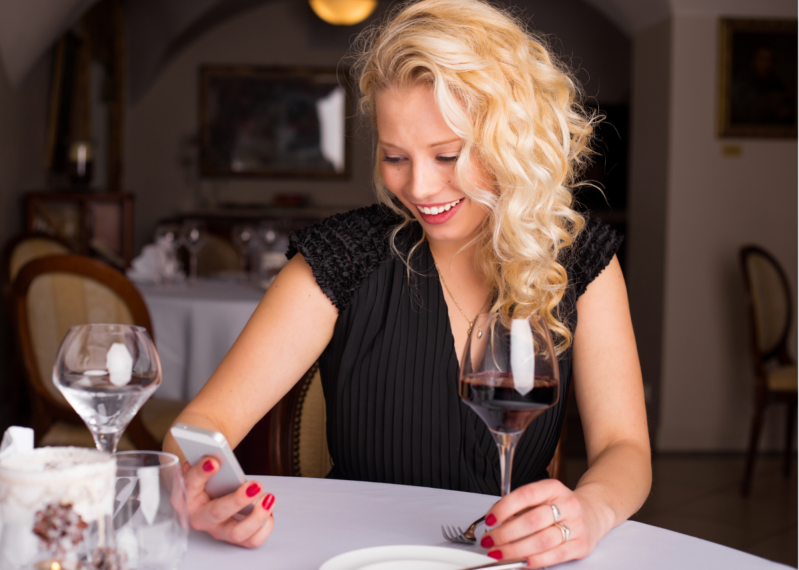 blonde woman with glass of red wine looking at cell phone