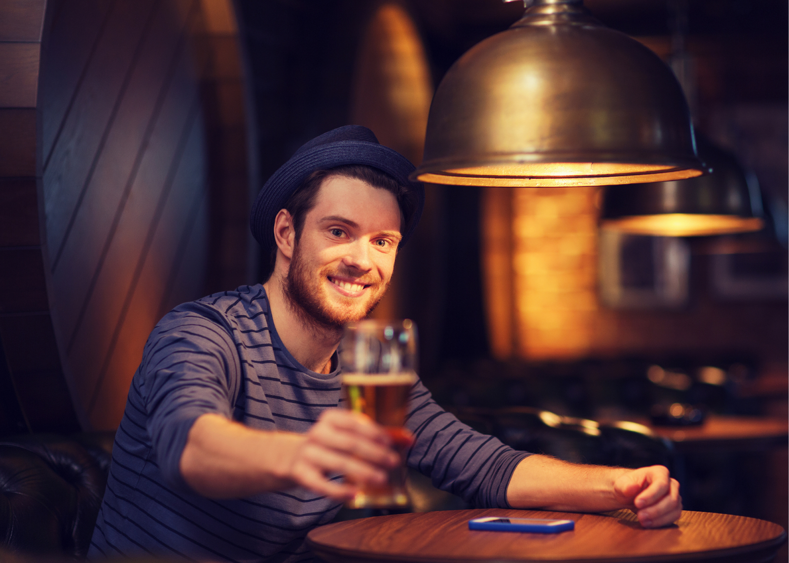 man in blue hat passing a beer