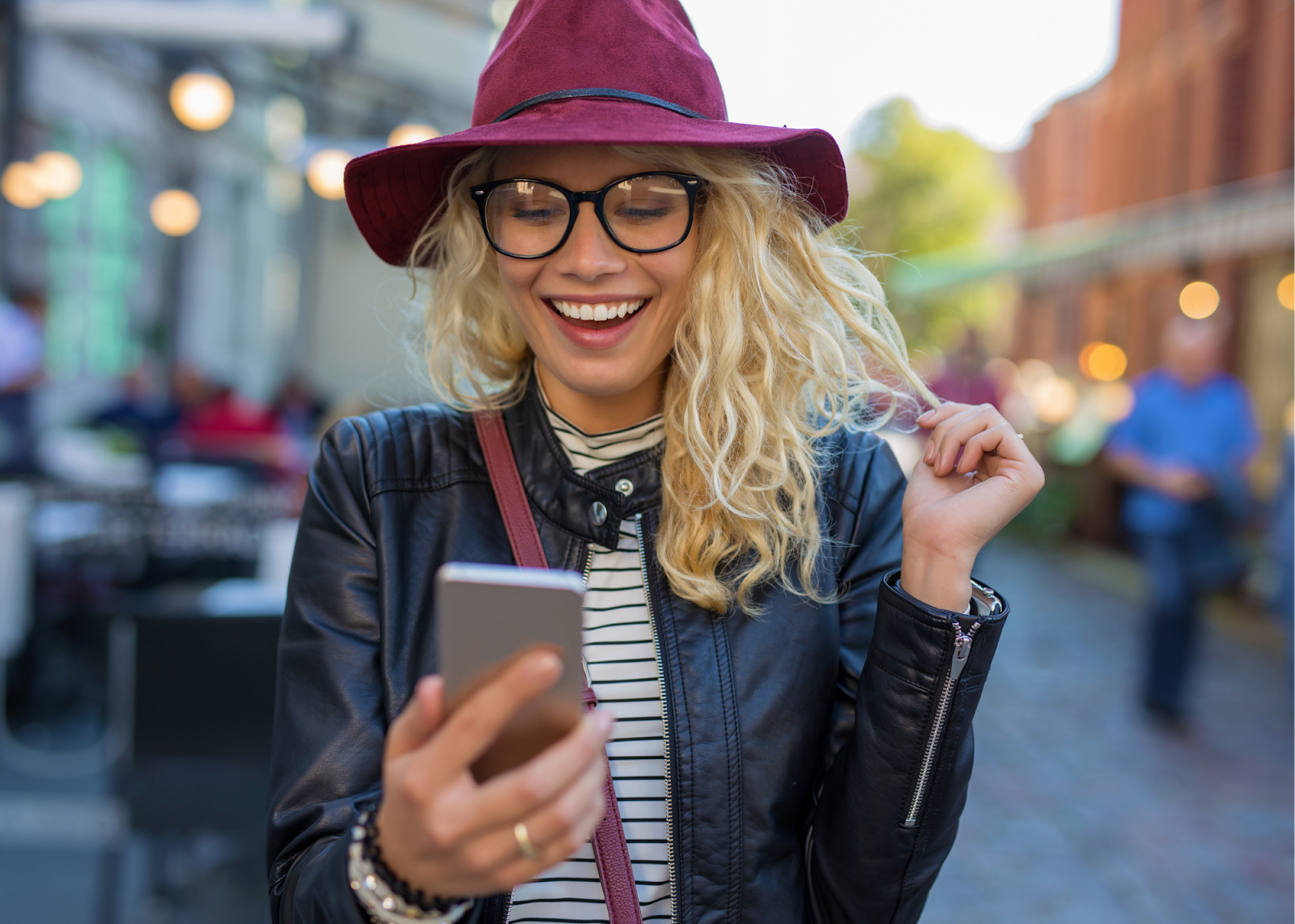 blonde girl with purple hat smiling at phone